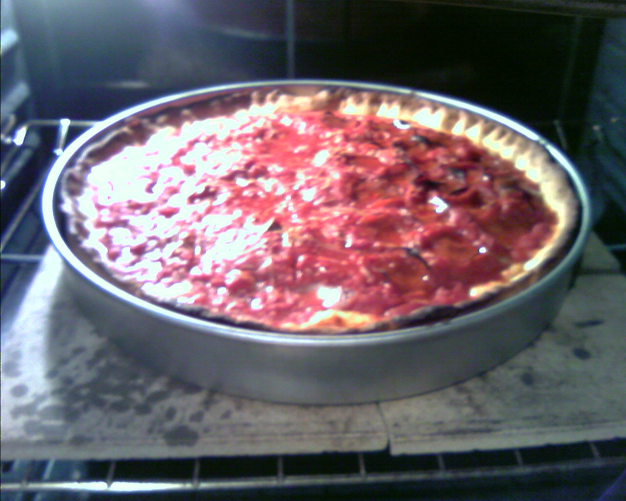 photo of my very first home made deep dish pizza, inside the oven on top of a pizza stone.
