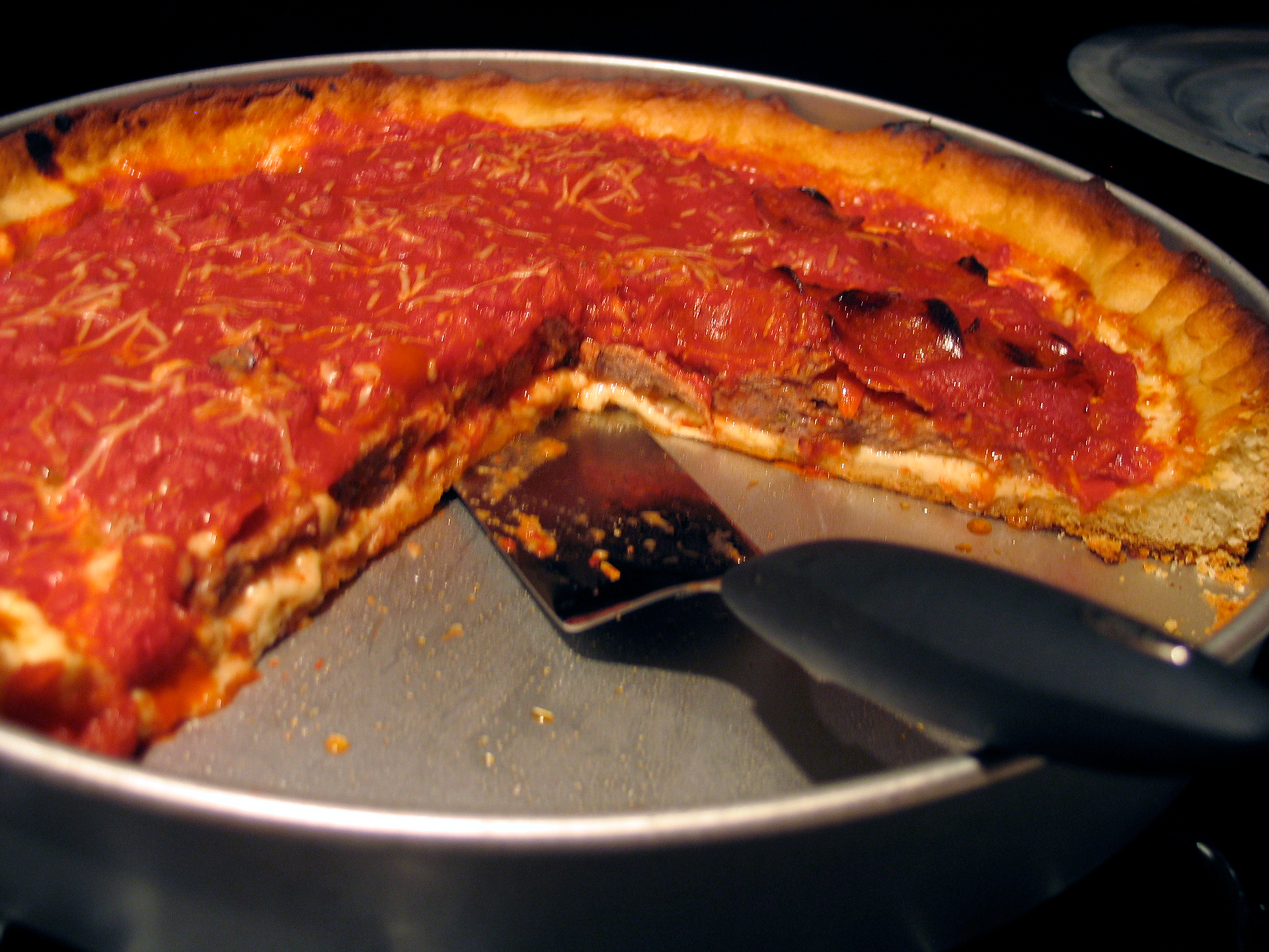 photo of my first home made deep dish pizza in the pan with serving spatula, with slices removed